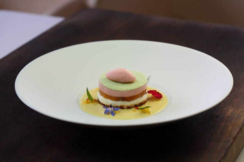 Cheesecake con pesche al prosecco, salsa all'acqua di rose e parfait al prezzemolo