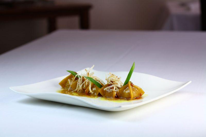 Il tortello ripieno di pollo in potacchio cotto nel tè al rosmarino e cipolla sotto la cenere e croccante di cipollotto