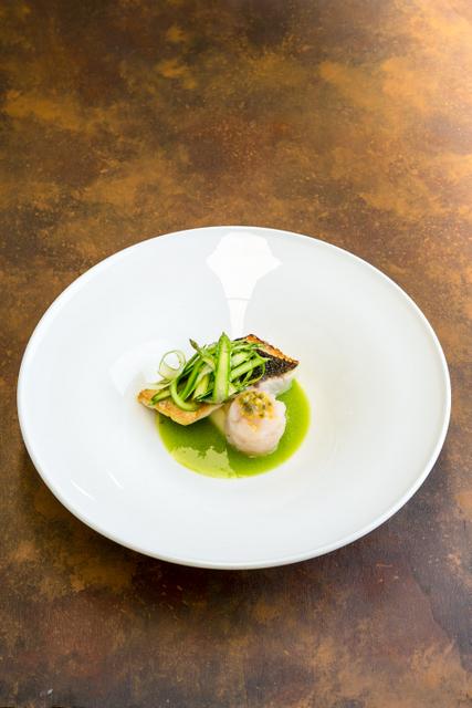 Branzino con pelle croccante su acqua di asparagi verdi, tartare di branzino, cialda di polenta e frutto della passione